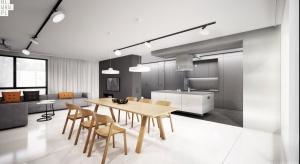 Połączenie betonu zinnymi materiałami oraz odpowiednie wyeksponowanie pozwoliło stworzyć nowoczesne wnętrze w industrialnym stylu. Dominują tu odcienie szarości i biel, a drewniany stół i krzesła idealnie dopełniają całości.