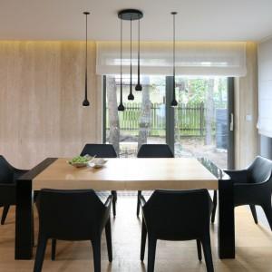 Ta jadalnia to uosobienie eleganckiej nowoczesności. Prostemu, drewnianemu stołowi towarzyszą czarne, nowoczesne krzesła. Z siedziskami harmonizują liczne wiszące lampy w czarnym kolorze i smukłym kształcie, rozszerzającym się ku dołowi. Projekt: Katarzyna Kiełek. Fot. Bartosz Jarosz.