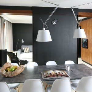 Oświetlenie nad stołem nawiązuje formą do tradycyjnej, biurowej lampki. Taki kształt prezentuje się nowocześnie, idealnie wpisując się w przestrzeń jadalni. Biała barwa kloszy sprawia, że lampy są mocno wyeksponowane na tle ciemnej, czarnej ściany. Projekt: Kasia i Michał Dudko. Fot. Bartosz Jarosz.