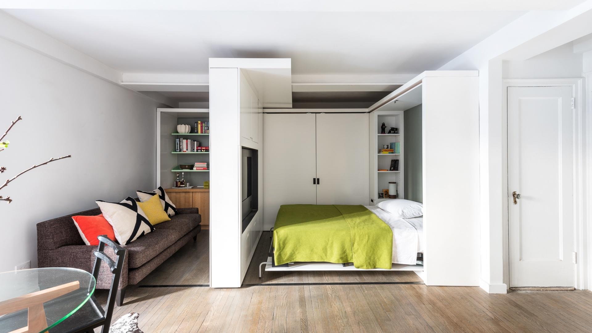 Drzwi garderoby można zamknąć, tworząc funkcję sypialni. Przy łóżku zaplanowano kilka praktycznych półek, przeznaczonych na książki do lektury przed snem. Zostały one oddzielone od większej biblioteczki w gabinecie przez obecność garderoby. Projekt: MKCA. Fot. Alan Tansey.