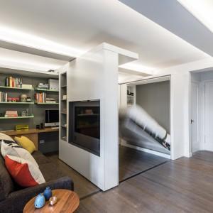 W kilka chwil, za pomocą przesuwnej ścianki działowej można wygospodarować miejsce na sypialnię. Łóżko na dzień chowane jest w ścianie i za panelem z TV. Projekt: MKCA. Fot. Alan Tansey.