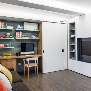 Gdy ścianka pozostaje w swoim pierwotnym miejscu, domownicy mogą pracować w gabinecie lub relaksować się na sofie przed telewizorem. Projekt: MKCA. Fot. Alan Tansey.