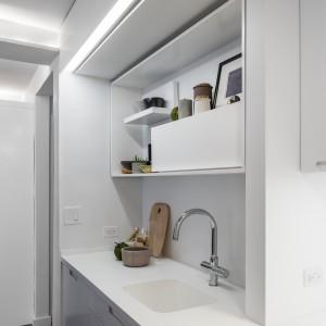 """Z blatem w strefie zmywania zlicowano biały zlewozmywak jednokomorowy, który dzięki kolorystyce """"znika"""" w białej kuchni. Projekt: MKCA. Fot. Alan Tansey."""