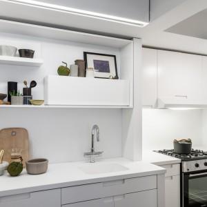 Zabudowę w kuchni utrzymano w modnej, współczesnej stylistyce i białym kolorze. Matowe, białe fronty nadają przestrzeni elegancki charakter, a delikatne akcenty w czarnym kolorze przebijają dominującą biel. Projekt: MKCA. Fot. Alan Tansey.