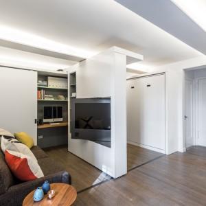 W skład mobilnej ścianki wchodzi element, którym można sterować indywidualnie. Panel TV możemy przekręcić o 180 stopni, dzięki czemu telewizję oglądać można zarówno z poziomu salonu, jak i w sypialni. Projekt: MKCA. Fot. Alan Tansey.