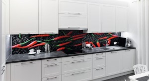 Życzeniem inwestorów była kuchnia urządzona w sposób klasyczny, ale też z ostrym akcentem. Dlatego właśnie powstała dekoracyjna ściana nad blatem z papryczkami chilli.