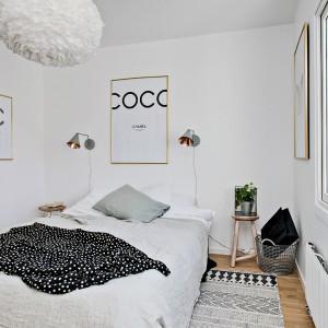 Z salonu można bezpośrednio przejść do sypialni, w której umieszczono duże łóżko, nad którym zawisła dekoracyjna, tekstylna lampa. Fot. Fredrik J Karlsson/Alvhem Makleri.