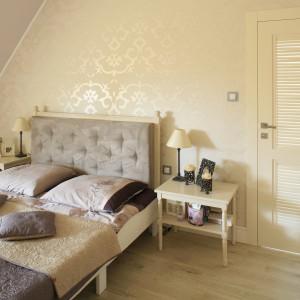 Ścianę za łóżkiem wykończono kremową tapetą z eleganckim wzorem. Perłowy połysk sprawia, że wnętrze nabiera luksusowego szyku. Projekt: Karolina Łuczyńska. Fot. Bartosz Jarosz.