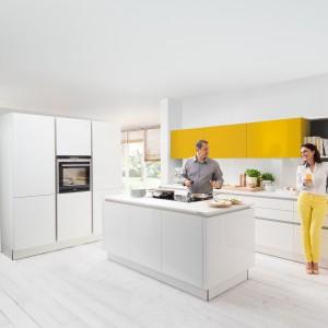 W zdominowanej przez biel jasnej kuchni, rząd górnych szafek z żółtymi frontami stanowi element, ożywiający aranżację. Kuchnia z takim kolorowym detalem pozostaje elegancka i ponadczasowa. Fot. Nolte Kuechen, meble Curry Hochglanz.