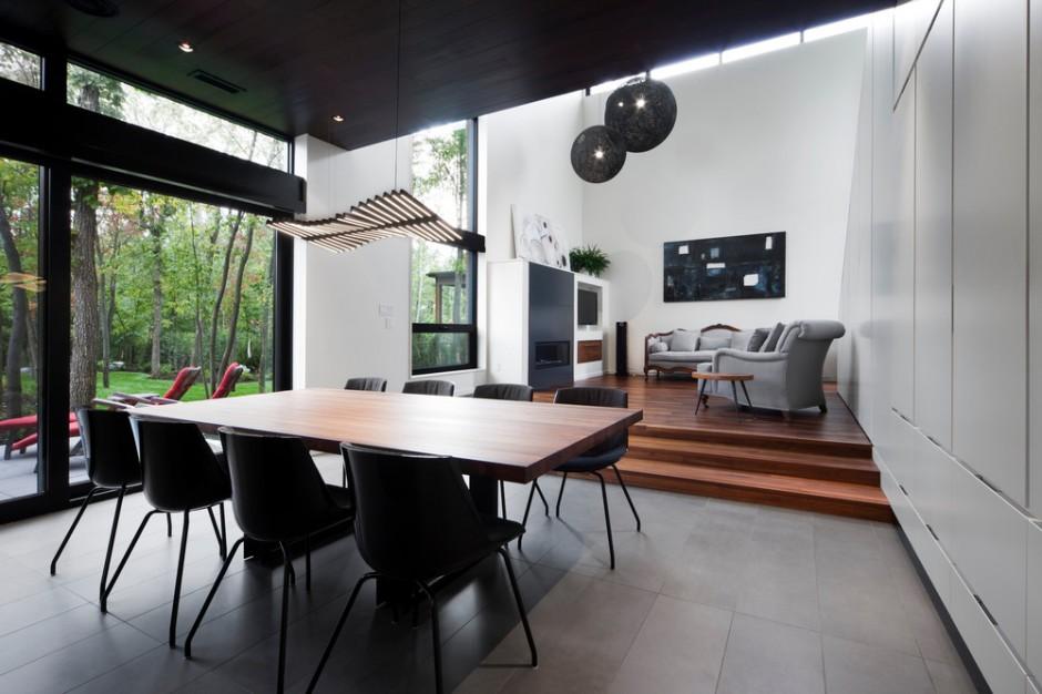 Na parterze urządzono przestronną strefę dzienną. Kuchnia z jadalnią zajęły niższą część kondygnacji, gdzie podłogę zrównano z tarasem, a salon został usytuowany na delikatnym podeście z drewna. Projekt: Blouin Tardif Architecture-Environnement. Fot. Steve Montpetit.