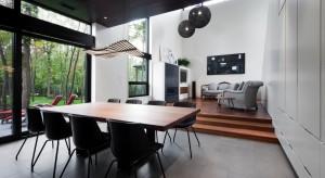 Minimalistyczne wnętrze dzięki drewnianym akcentom i otaczającej dom zieleni jest jednocześnie nowoczesne i bardzo przytulne.