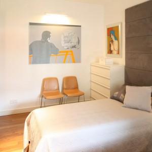 Grafiki w ciepłych kolorach sprawiają, że wnętrze jest jedyne w swoim rodzaju. Elegancki charakter nadaje mu przytulna, tapicerowana ściana za łóżkiem. Projekt: Małgorzata Galewska. Fot. Bartosz Jarosz.