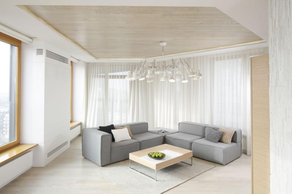 Nieco surowy salon urządzony został w minimalistycznym duchu. Główną jego ozdobą jest drewniany sufit oraz imponujących rozmiarów lampa-pająk. Projekt: Maciej Brzostek. Fot. Bartosz Jarosz.