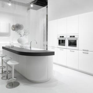 Ultra-nowoczesna kuchnia z oryginalnymi meblami o opływowym kształcie została wykończona niemal w całości w bieli. Jedynym elementem przełamującym jej dominację jest ciemny blat, wieńczący wyspę. Fot. Rational, model Onda.