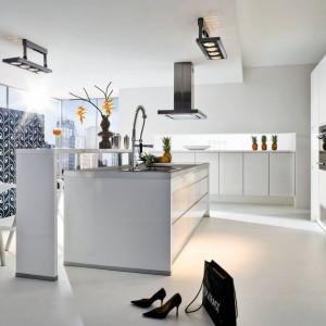 Nowoczesna kuchnia w bieli, wysokim połysku i ze stalowymi detalami. Na wyspę nałożono wyższy element, który pełni funkcję baru. Fot. Wellmann, model Avior.
