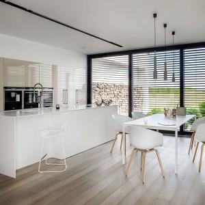 Elegancka, luksusowa kuchnia utrzymana w minimalistycznym stylu. Fronty wysokiej zabudowy wykończone są w błyszczącym, kremowym lakierze, a obszerna wyspa ma fronty polakierowane w kolorze złamanej bieli i macie. Fot. Zajc Kuchnie, model Z7.