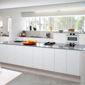 Długa wyspa kuchenna z białymi, matowymi frontami i szarym, połyskującym blatem stanowi punkt centralny tej nowoczesnej kuchni. Ciekawym detalem jest cokół mebla wykonany z bielonego drewna. Fot. Ballingslov.