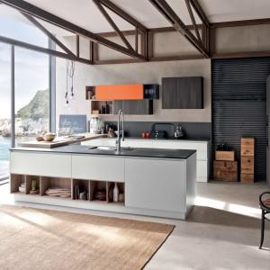 Kuchnia, w której postawiono na połączenie różnych barw. Wyspa kuchenna i dolna zabudowa pod ścianą są białe, połączone ze sobą drewnianym blatem. Górne szafki natomiast są ciemnoszare - kolorystycznie dopasowane do blatu. Fot. Stosa Cucine, model Replay.