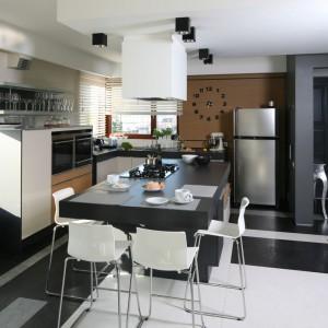 W tej kuchni w stylu delikatnie loftowym dominuje ciemna szarość i biel. Nad wyspą z grubym blatem zawisł biały okap o prostokątnym kształcie. Kolorem harmonizuje z krzesłami towarzyszącymi wyspie. Projekt: Małgorzata Borzyszkowska. Fot. Bartosz Jarosz.