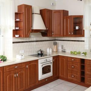 Do klasycznej kuchni idealnie pasuje okap w klasycznym stylu. Utrzymano w kremowym kolorze i z aplikacjami w barwie drewna, harmonizującej z wybarwieniem drewnianych mebli stanowi idealne uzupełnienie aranżacji tej kuchni. Projekt: Małgorzata Goś. Fot. Bartosz Jarosz.