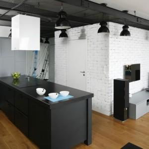 Duży, solidny ciemnoszary półwysep stanowi centrum tej urbanistycznej kuchni. Obecność okapu zaznacza kontrastująca z ciemną szarością biel, którą wykończono jego ścianki. Tym samym, wyciąg nawiązuje do barwy cegły na ścianie. Projekt: Monika i Adam Bronikowscy. Fot. Bartosz Jarosz.