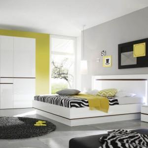 Zestaw Neve II to nowoczesne meble z białymi, lakierowanymi frontami przełamanymi detalami w kolorze koniaku. Łóżko z podświetlanym wezgłowiem. Zestaw dostępny w sklepie Furnite.pl. Fot. Furnite.pl.