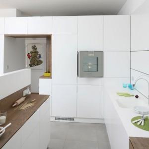Ultra-nowoczesna wysoka zabudowa staje się w tej kuchni także elementem działowym, z wnęką prowadzącą do sąsiadującego z kuchnią pomieszczenia. Matowa biel nadaje całości elegancki charakter. Projekt: Konrad Grodziński. Fot. Bartosz Jarosz.