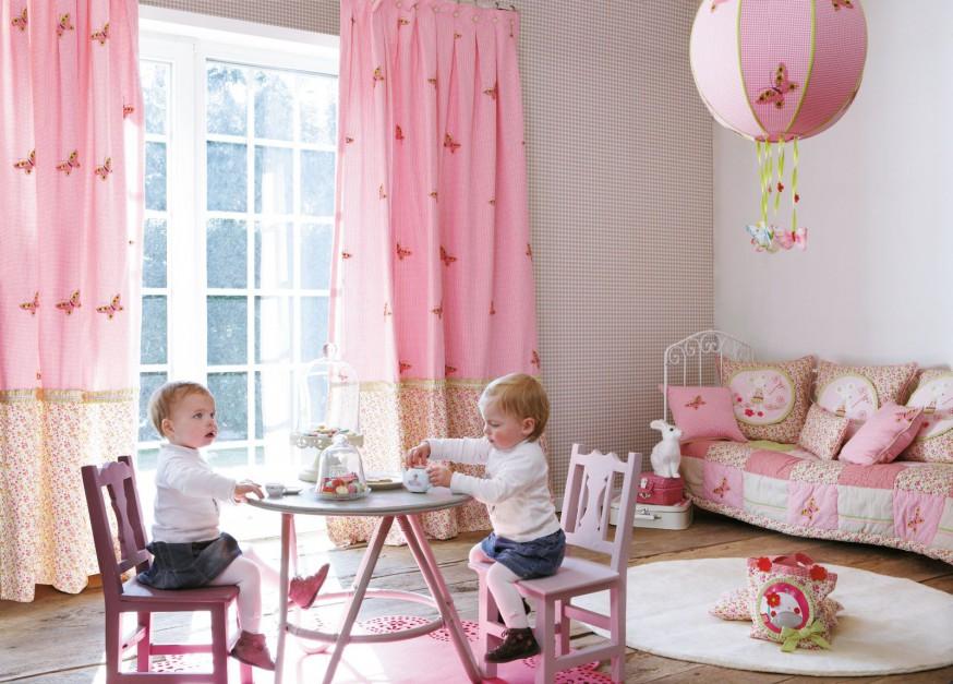 Lekki urok aranżacji to bez wątpienia zasługa różowej tkaniny w czerwone motylki, z której uszyto zasłony, narzutę na łóżko, miękkie poduszki oraz dekoracyjny abażur. Dodatki z kolekcji Lollipops francuskiej marki Casadeco. Fot. Casadeco.
