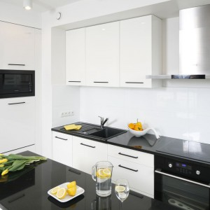 Biel kuchennej zabudowy elegancko podkreślają czarne, kamienne blaty, nawiązujące do ściany w salonie. Projekt: Katarzyna Uszok. Fot. Bartosz Jarosz.