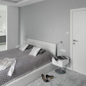 Sypialnia, podobnie jak pozostałe pomieszczenia w domu jest elegancka i urządzona minimalistycznie. Dominują tutaj modne szarości. Za przesuwnymi szklanymi drzwiami znajduje się łazienki pani i pana domu. Projekt: Katarzyna Mikulska-Sękalska. Fot. Bartosz Jarosz.