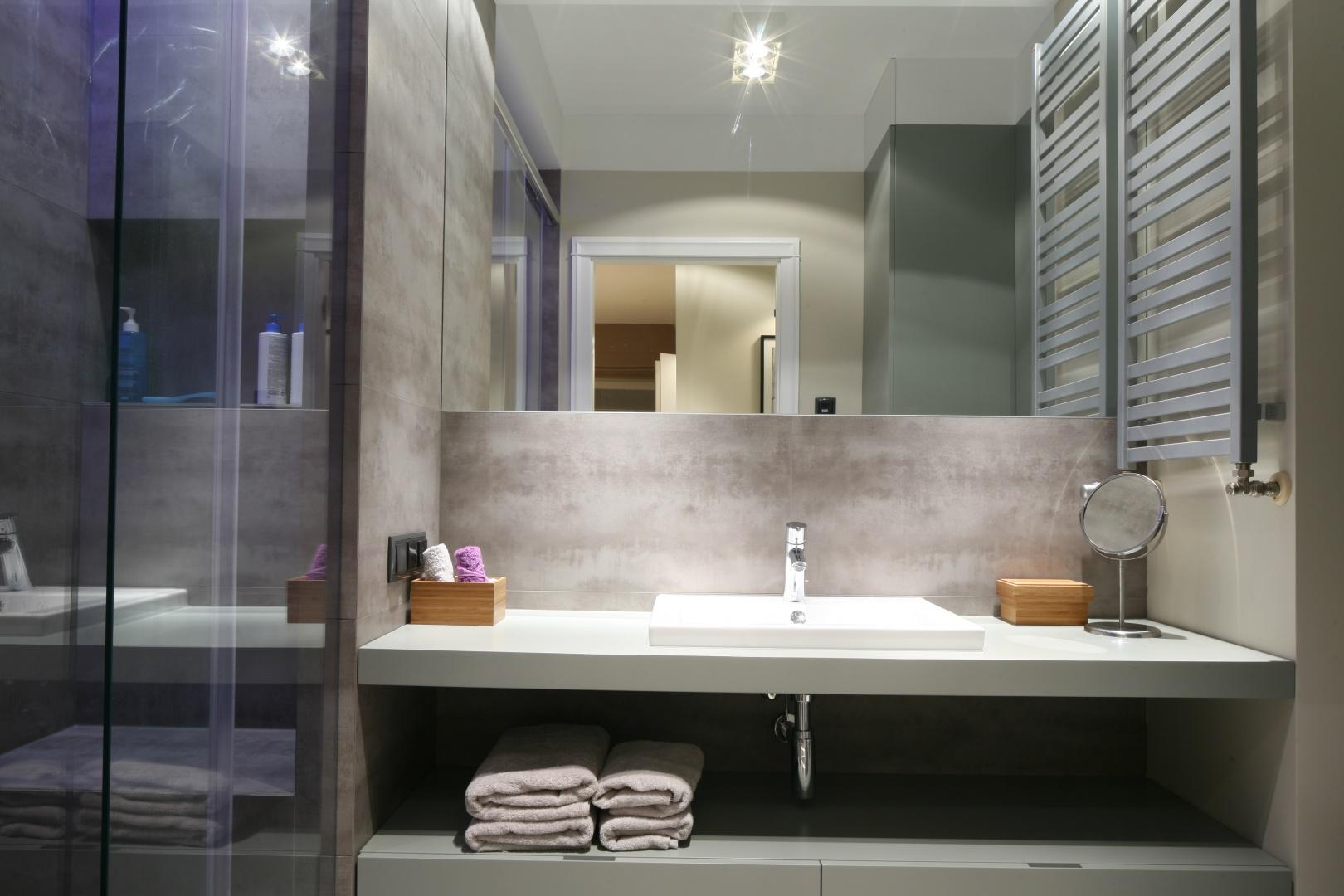Lustro sięgające do samego sufitu optycznie powiększa wnętrze małej łazienki. W pomieszczeniach o niewielkim metrażu zastosowanie wielkoformatowych, połyskujących powierzchni pozytywnie wpływa na odbiór wnętrza. Projekt: Lucyna Kołodziejska. Fot. Bartosz Jarosz.