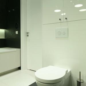W małych łazienkach warto wprowadzać połyskujące powierzchnie. Dobrze sprawdzą się lakierowane na wysoki połysk fronty mebli. Projekt: Agnieszka Ludwinowska. Fot. Bartosz Jarosz.