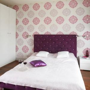 Pikowane łóżko w kolorze bakłażana nadaje aranżacji glamourowy charakter. Niemniej atrakcyjna jest ściana, będąca tłem dla mebla, którą ozdobiono tapetą w liliowe wzory. Projekt: Beata Ignasiak. Fot. Bartosz Jarosz.