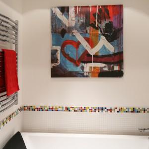 Biała łazienkę ożywia nowoczesny obraz wiszący nad wanną oraz kolorowe listwy, które poziomą linią przecinają biała powierzchnię ścian. Wykonano je z kolorowej mozaiki. Projekt: Dorota Szafrańska. Fot. Bartosz Jarosz.