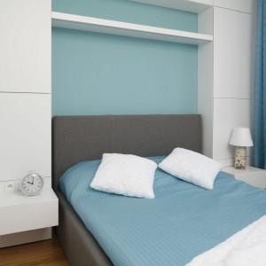 W sypialni ściana nad łóżkiem została zabudowana. Taki schowek jest znacznie pojemniejszy niż wolno stojący mebel i dodatkowo nie przytłacza pomieszczenia. Fronty i szafki nocne wykonane z płyty MDF lakierowanej na wysoki połysk, powiększają wnętrze.
