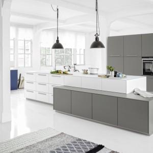 W tej przestronnej kuchni centralne miejsce zajmuje duża, funkcjonalna wyspa. Biel połączona została w elementami w kolorze szarym, co nadaje wnętrzu nowoczesny, ale i elegancki charakter. Fot. Nolte Kuechen, model Soft Lack.