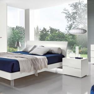 Jeśli chcemy, aby nowoczesna biała sypialnia zyskała elegancki wygląd, zafundujmy sobie kilka dodatków w ciemnym kolorze. Granatowa narzuta i puf sprawią, że białe meble zyskają nowy wygląd. Na zdjęciu: kolekcja mebli dostępna w ofercie marki Giessegi. Fot. Giessegi.