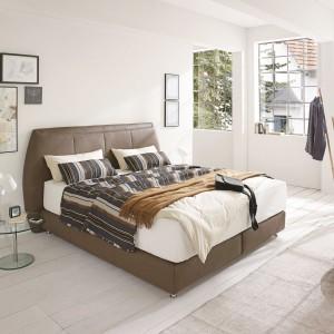 Ciekawym sposobem, na lekkie ocieplenie białej sypialni jest łóżko wykończone brązową skórą ekologiczną, np. z serii Premium marki Ada. Takie wykończenie ociepla wnętrze, a przy tym nadaje mu luksusowy wygląd. Fot. Ada.