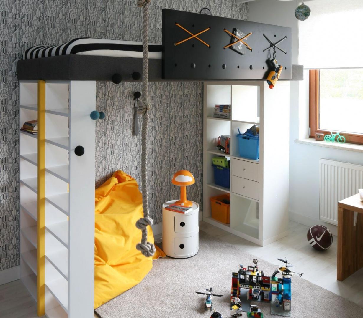 Chociaż wygląd łóżka przypomina piracki statek, służy nie tylko do snu i zabawy, lecz także sprytnie organizuje przestrzeń malucha. Wszystko za sprawą praktycznych półek, które są stałym miejscem stacjonowania czołgów, samolotów czy innych zabawek. Podłogę w tej części pokoju (również pod łóżkiem) wykończono miękką wykładziną, tworząc bezpieczną przestrzeń do zabawy. Projekt: Katarzyna i Michał Dudko. Fot. Bartosz Jarosz.