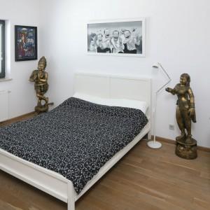 Lekkie, humorystyczne grafiki urozmaicają wygląd białej sypialni w nowoczesnym stylu. Z dekoracjami ściennymi harmonizują mosiężne figurki ustawione przy łóżku. Projekt: Konrad Grodziński. Fot. Bartosz Jarosz.