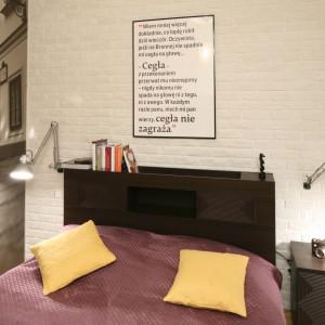 Ścianę za łóżkiem wykończono białą cegłą, która podkreśla lekko loftową stylistykę wnętrza. Na samym środku zawieszono oprawiony w ramę plakat z tekstem, którego główną bohaterką jest cegła. Projekt: Iza Szewc. Fot. Bartosz Jarosz.