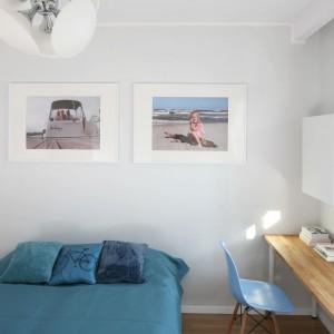 Białą sypialnię warto wzbogacić w kolory. To wnętrze, mimo ciepłego elementu w postaci drewnianego biurka jest dość surowe. Kolor niebieski dodaje sypialni klimatu i energii. Projekt: Anna Maria Sokołowska. Fot. Bartosz Jarosz.