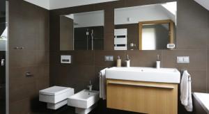 Łazienka urządzona na poddaszu utrzymana jest w nowoczesnym stylu. Ciemny odcień płytek połączony z bielą i geometryczna formą ceramiki dodaje wnętrzu elegancji.