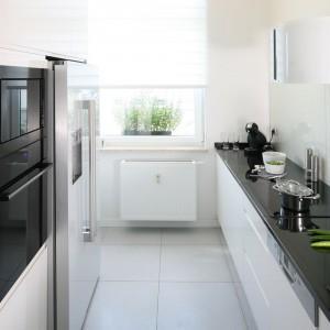 Wąską kuchnię urządzono w bieli, która optycznie powiększa jej przestrzeń. Zabudowa meblowa, poprowadzona w dwóch rzędach, po jednej stronie skrywa niezbędny sprzęt AGD, po drugiej - eksponuje dekoracyjny okap. Projekt: Anna Maria Sokołowska. Fot. Bartosz Jarosz.