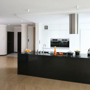W przestronnym apartamencie zintegrowaną przestrzeń kuchni od salonu oddziela długi półwysep, na którym znajduje się w pełni zintegrowana strefa przygotowywania posiłków. Projekt: Izabella Korol. Fot. Bartosz Jarosz.