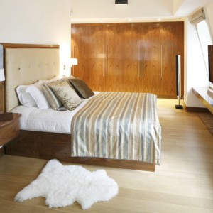 W eleganckiej sypialni ocieplonej drewnem telewizor zawieszono na ścianie z lekkim skosem. Poniżej monitora, na całej długości ściany rozciąga się drewniany blat, na którym ustawiono nowoczesny głośnik. Projekt: Studio KPP. Fot. Bartosz Jarosz.