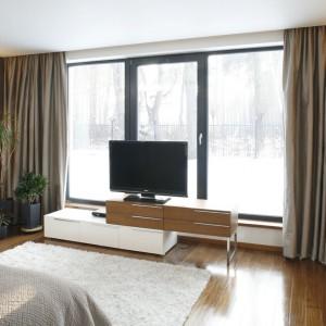 W przestronnej sypialni sprzęt RTV umieszczono na oryginalnej szafce, stawionej naprzeciw dużych przeszkleń. Dla zapewnienia lepszego obrazu na oknach zawieszono eleganckie zasłony. Projekt: Dąbrówka Potowska. Fot. Bartosz Jarosz.