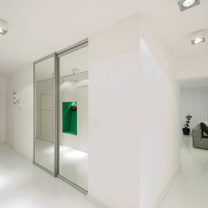 Mimo niemożności wyburzenia ścianki, oddzielającej strefę dzienną od holu, postarano się o to, aby optycznie powiększyć przestrzeń. Duże tafle luster idealnie spełniają to zadanie. Projekt: Radomír Minjarík. Fot. Juraj Hatina.