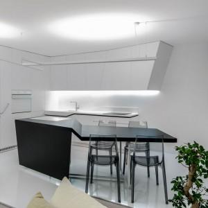 Na granicy kuchni i salonu stanęła oryginalna wyspa z blatem, który można rozkładać, otrzymując stół jadalniany. Projekt: Radomír Minjarík. Fot. Juraj Hatina.