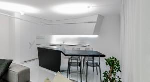 Mieszkanie niemal tonie w bieli, zaledwie gdzieniegdzie urozmaiconej ciemniejszymi akcentami. Monochromatyczna paleta barw i geometryczne formy tworzą ultra nowoczesne wnętrze.